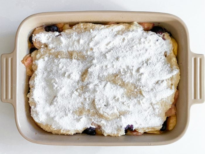 blueberry and peach cobbler topping, uncooked in 9 x 13 pan