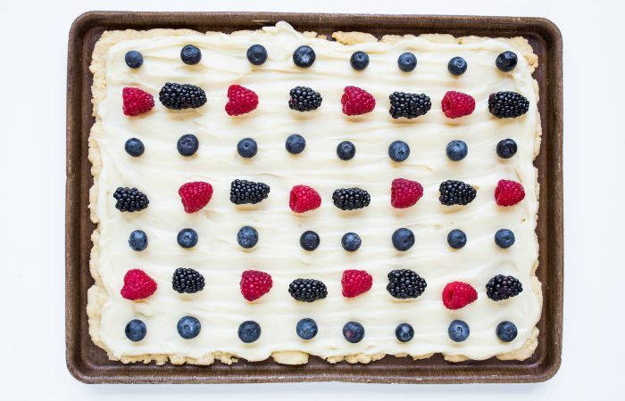 a baking sheet of sugar cookie bars with frosting and berries