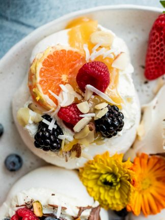 a mini pavlova with lemon curd, orange slice, berries, and coconut