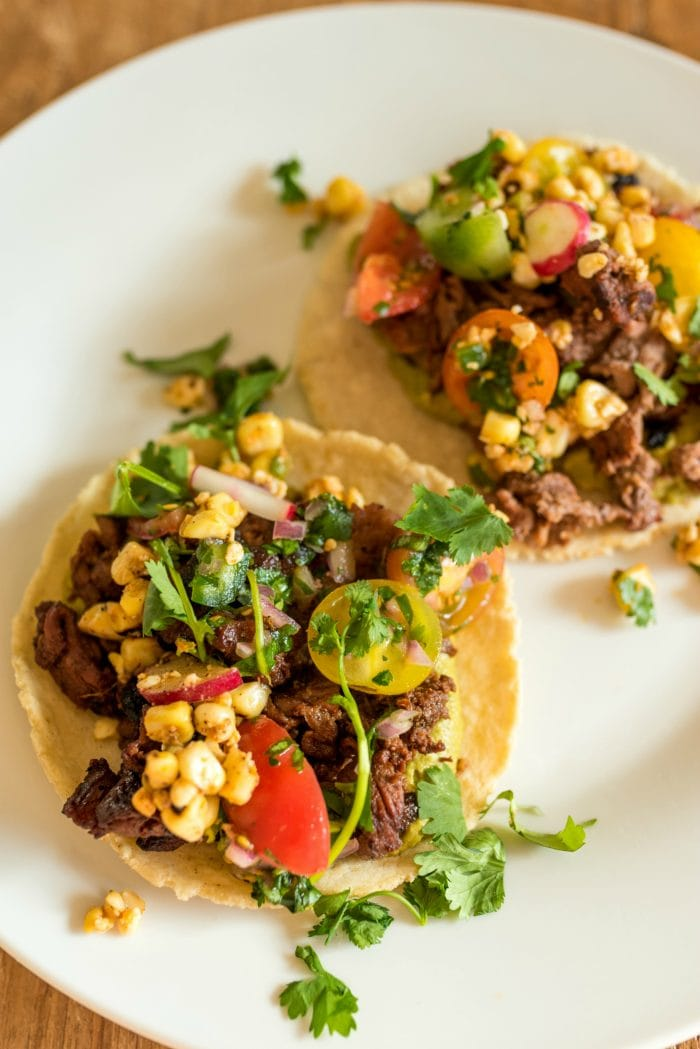 close up of taco with meat, corn salad, and salsa