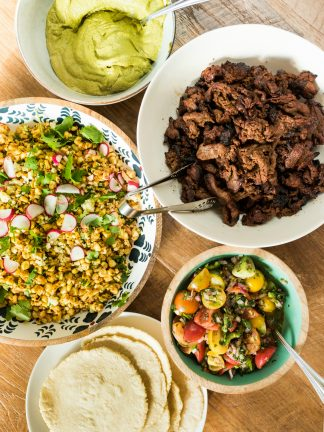 a taco spread with meat, corn salad, salsa, tortillas, and green sauce