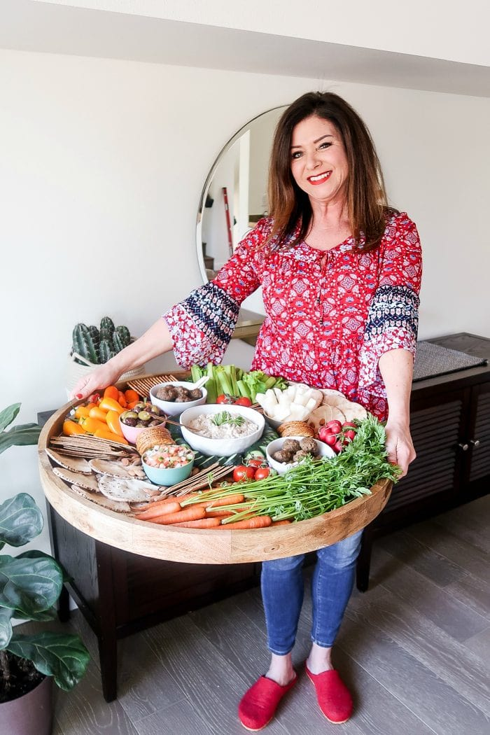 woman in red blouse holding an epic wood board filled with crudite veggies, dips, and more
