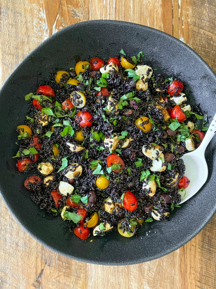 black bowl of black rice salad with cheese, tomatoes, and basil