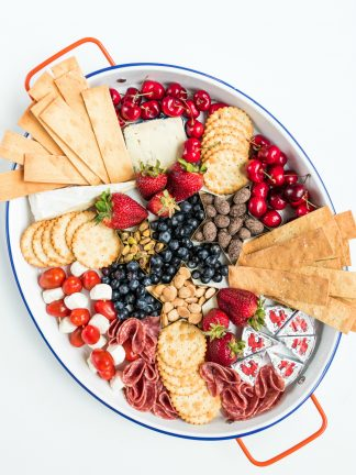 oval tray of cheese and crackers and fruit