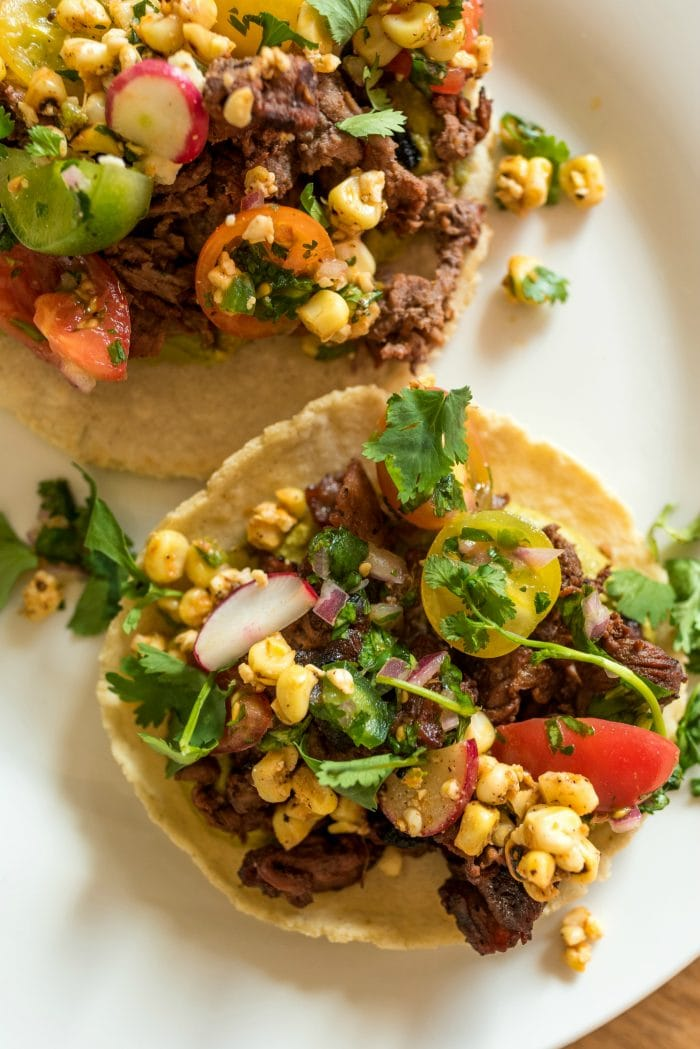 close up of taco with meat, corn salad, salsa, and garnished with cilantro
