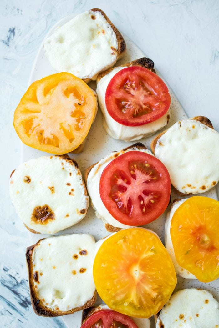 melted cheese on a roll with heirloom tomatoes