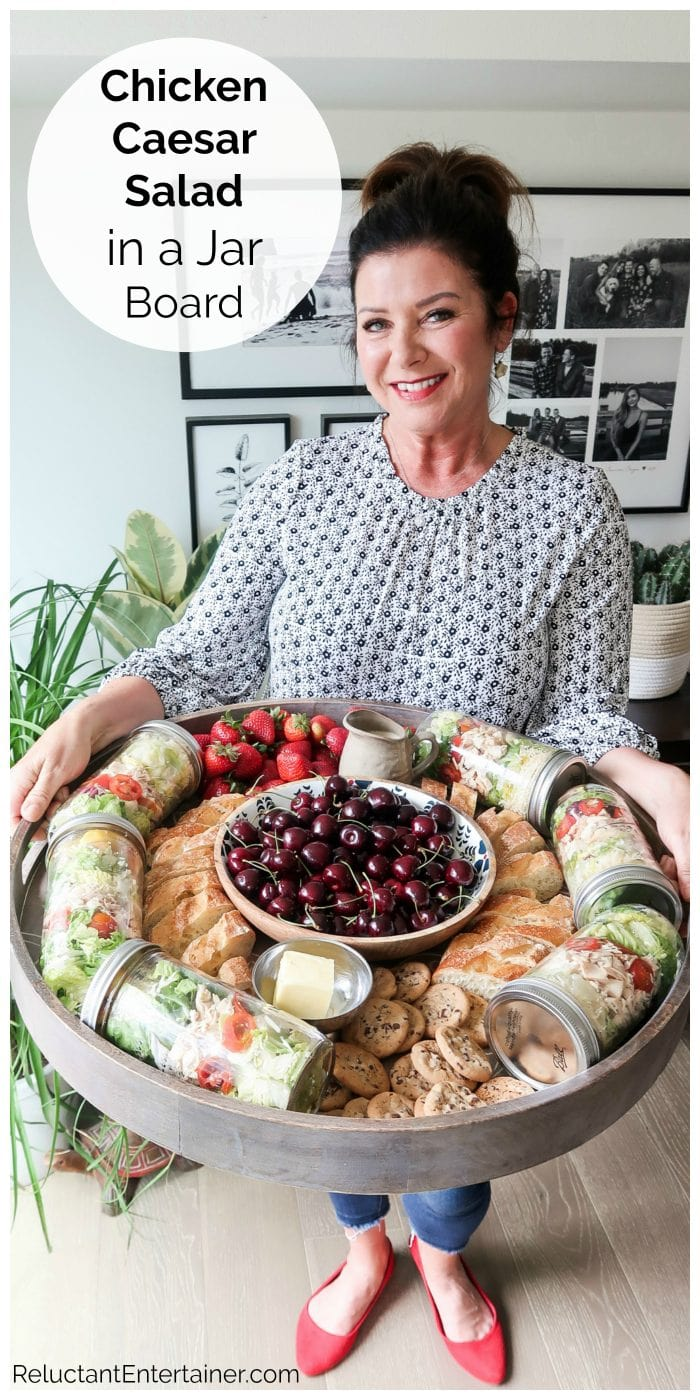woman holding a big wood board with salads in a jar, baguette bread, and a bowl of cherries