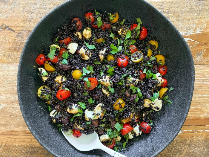 bowl of beautiful black rice salad with yellow and red tomatoes, cheese, and basil
