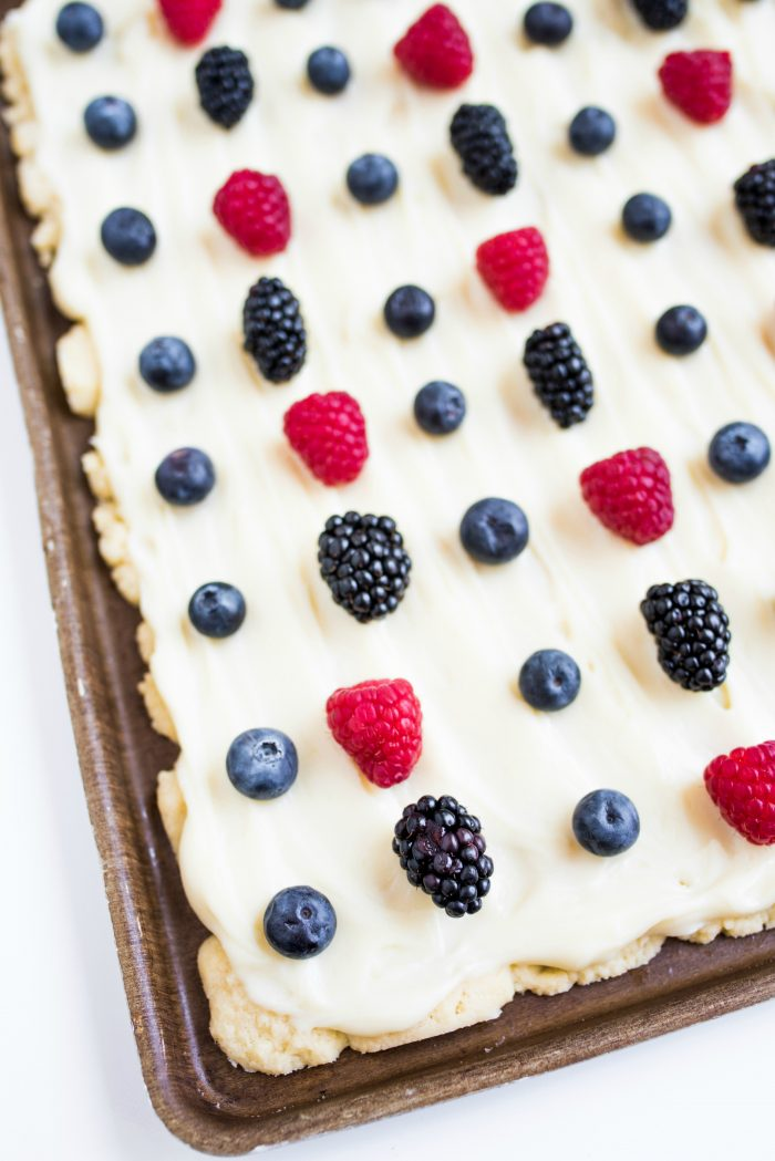 a baking sheet of sugar cookie bars with frosting and red and blue berries