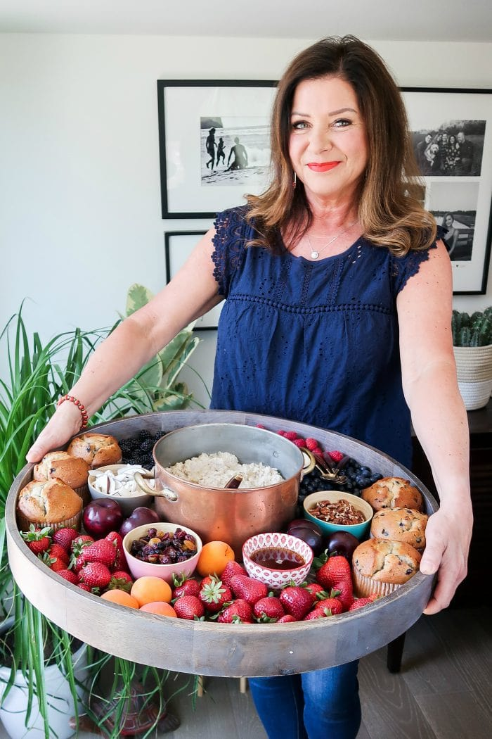 a woman holding a large round tray with a pot of oatmeal, fresh fruit, muffins and condiments in small bowls