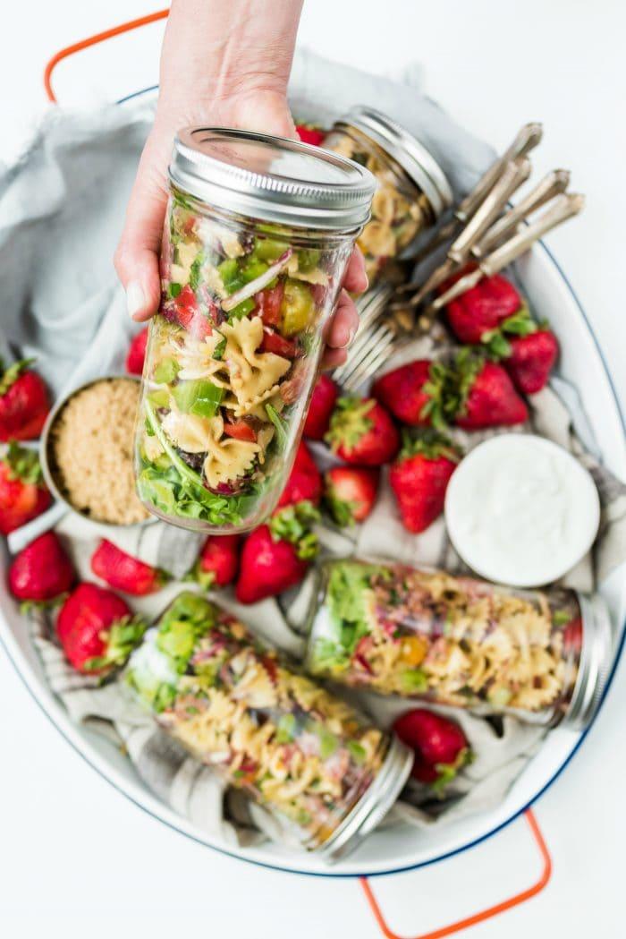 holidng a jar of bowtie pasta salad