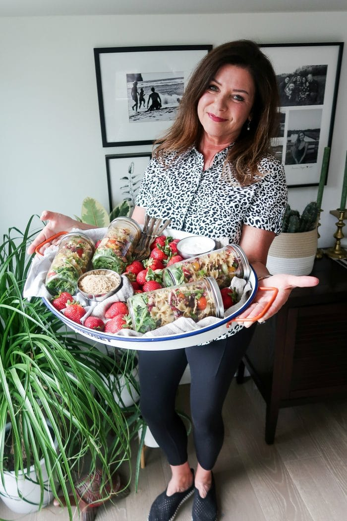 woman in black and white shirt holiding an oval tray with 4 jars of pasta salad, and strawberries