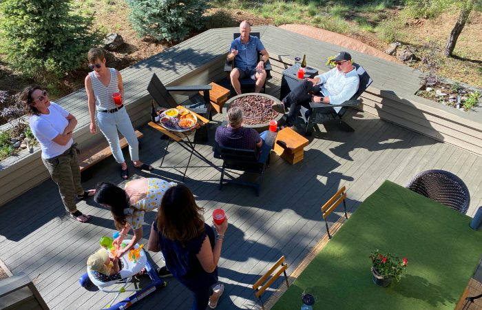 outdoor entertaining space with 6 people standing and sitting with drinks