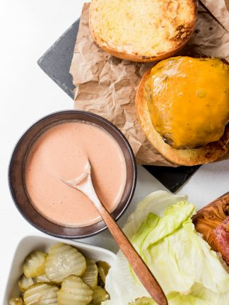 an open face cheeseburger with a small bowl of pink sauce