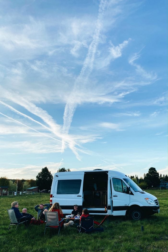 sprinter van in an open field with people sitting around