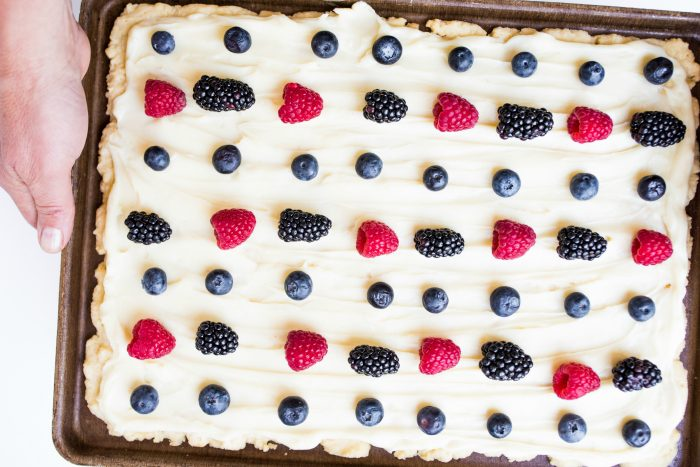 red, white, and blue dessert of sugar cookie bars with white frosting and red and blue berries