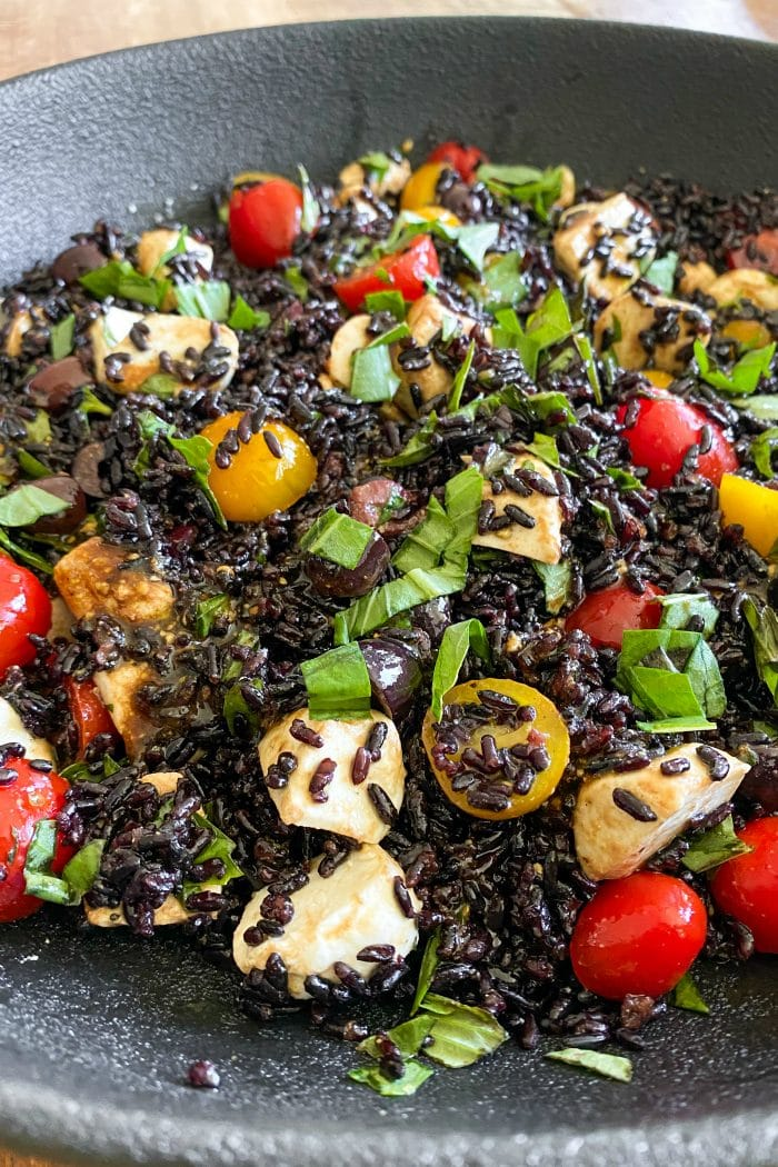 close up forbidden (black rice) salad with cherry tomatoes and mozzarella cheese balls