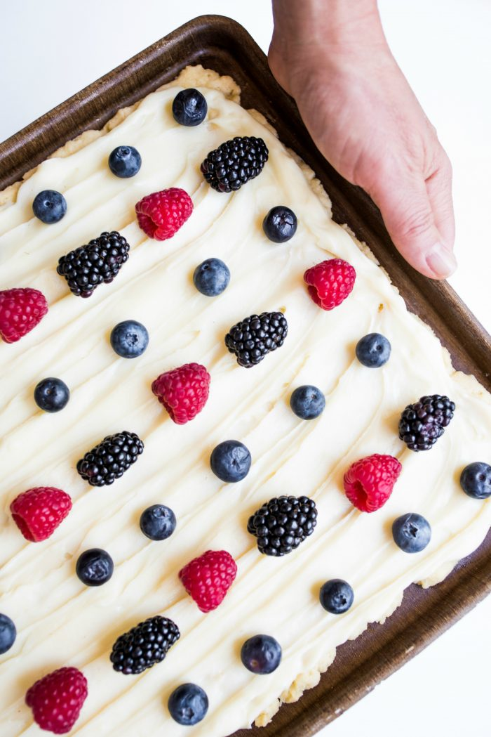 easy sugar cookie bars in a pan with white frosting and summer berries