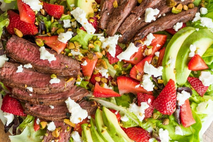 close up marinated balsamic steak slices on a bed of lettuce with strawberries, goat cheese, and avocado
