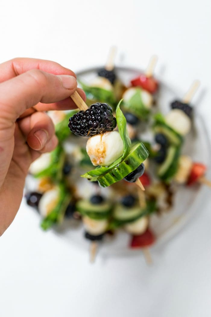 close up Summer Cucumber Bites on a Stick with a whole blackberry