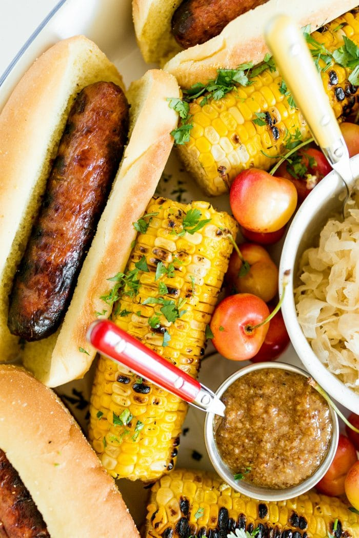 close up grilled brat on bun and grilled corn with mustard in small bowl
