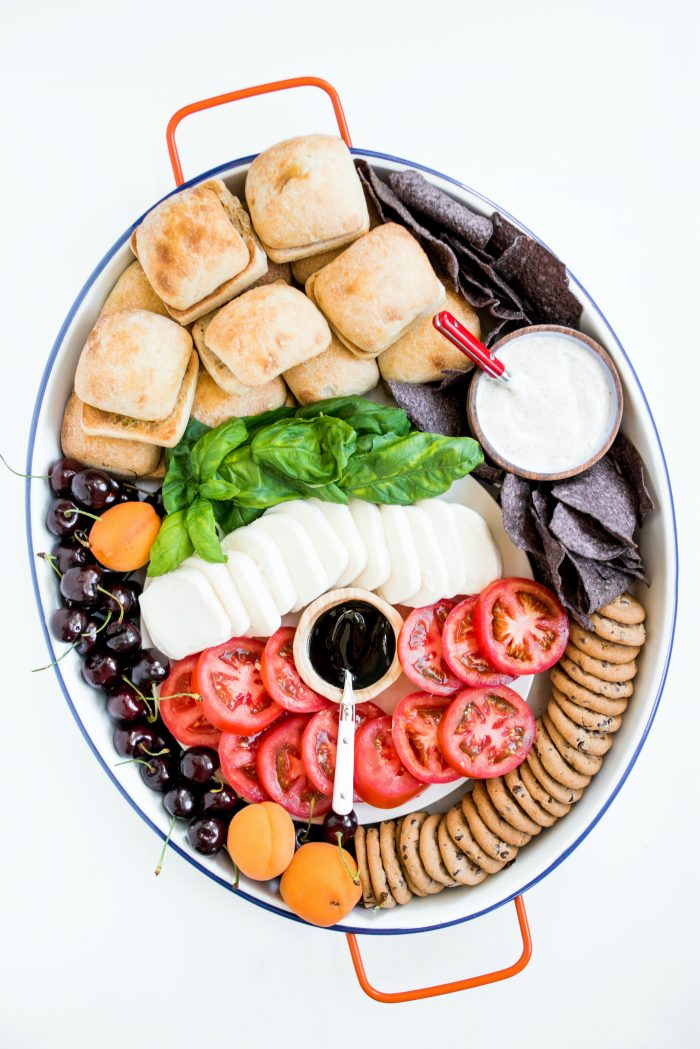 an oval board filled with caprese sandwich ingredients