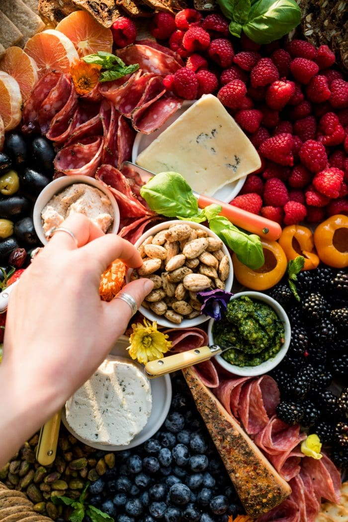 hand reaching into almond bowl on a beautiful colorful charcuterie