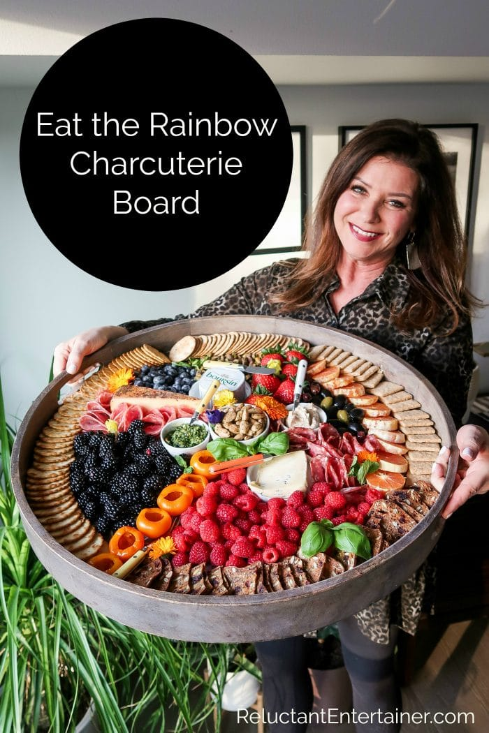 woman holding a round charcuterie board with colorful foods