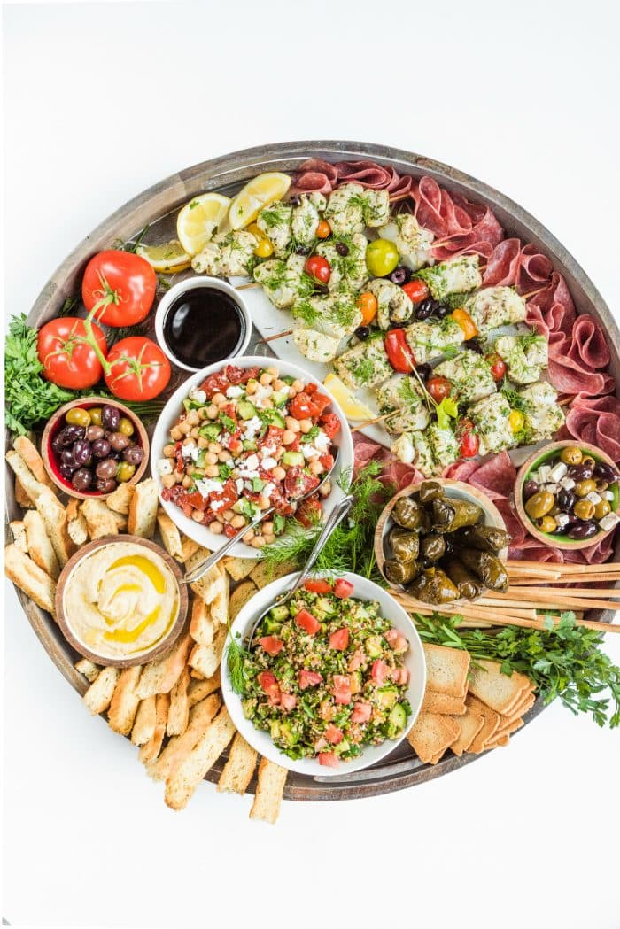 a beautiful round board filled with Summer Mediterranean food