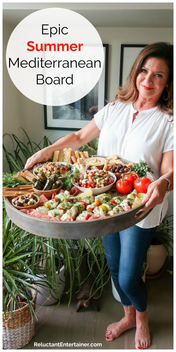 woman holding a dark gray round Epic Summer Mediterranean Board filled with charcuterie snacks