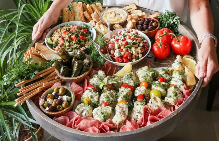 a person holding a big board filled with Mediterranean food