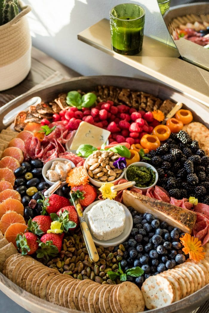 "looking down on a big round wood board filled with ""rainbow"" colored foods and charcuterie"