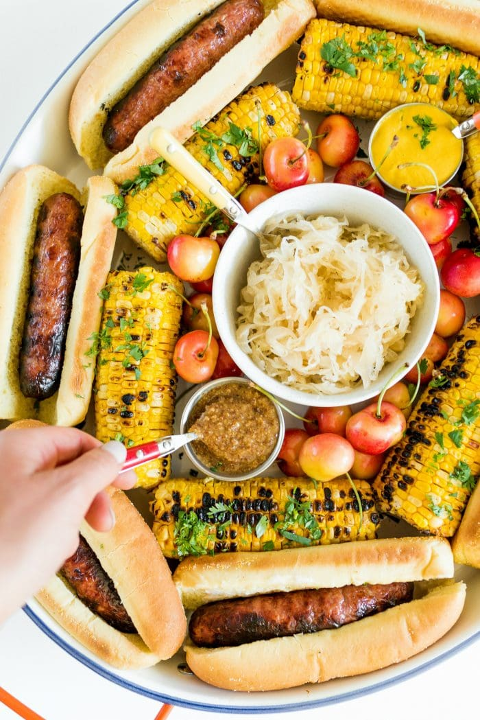 dipping a spoon into mustard on a Summer Brats and Sauerkraut Tray