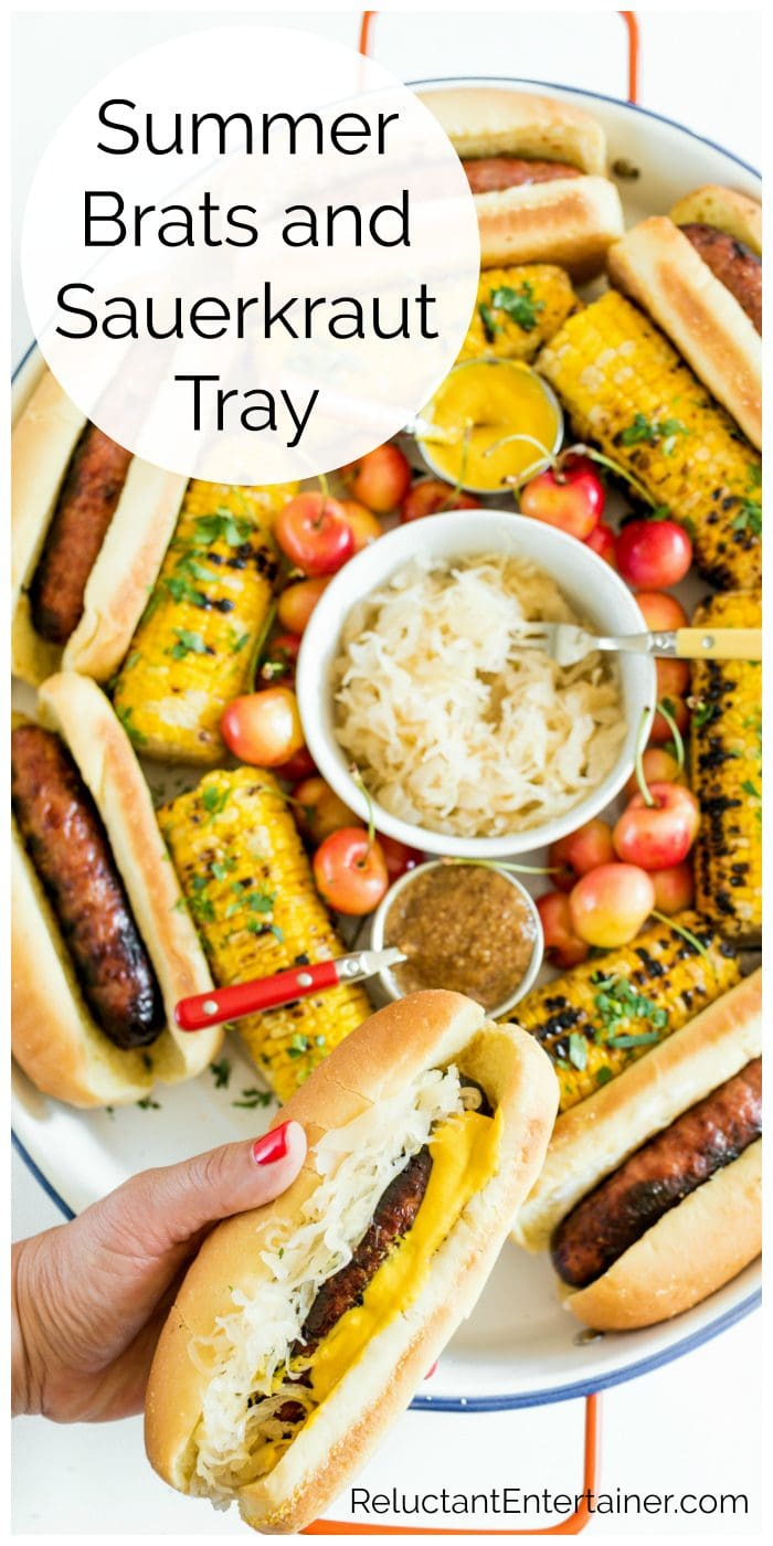 a tray filled with grilled brats, sauerkraut, grilled corn, and cherries
