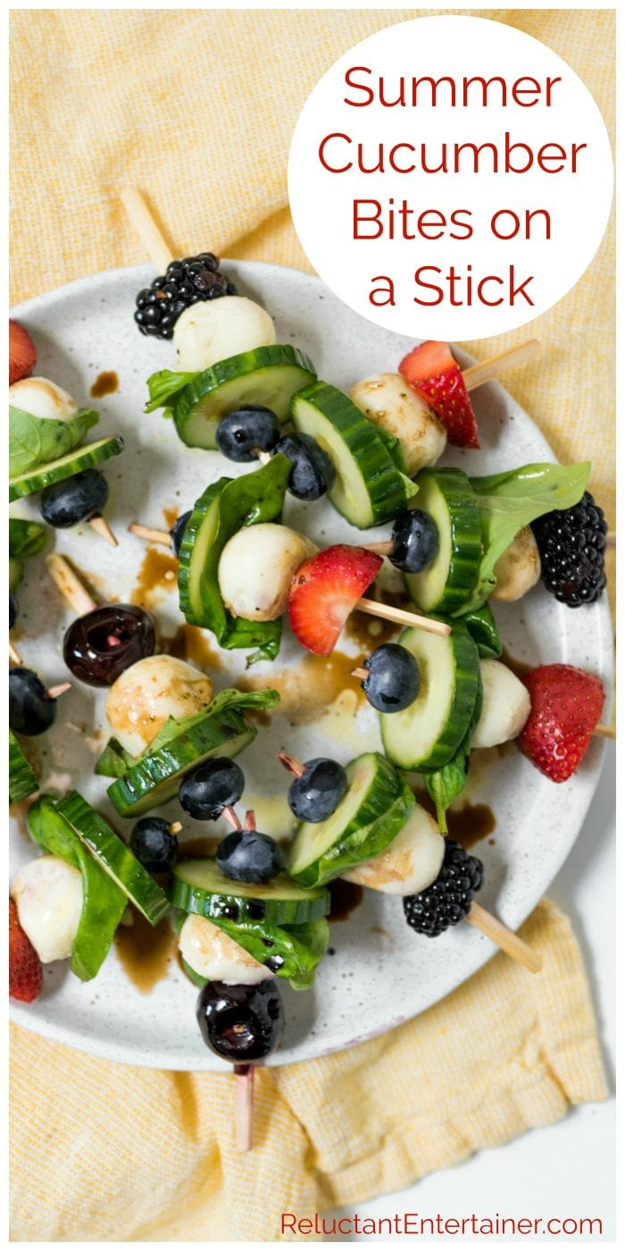A plate of Summer Cucumber Bites on a Stick with strawberries, cherries, blackberries, and blueberries