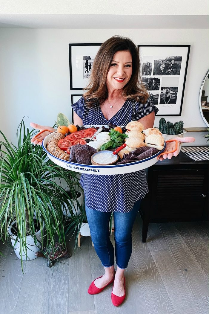 woman holding a tray of caprese sandwich slider ingredients