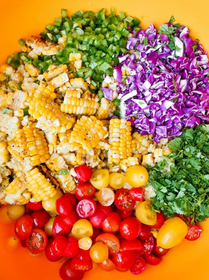 deconstructed ingredients for corn tomato salad with jalapeno, cabbage, and cilantro