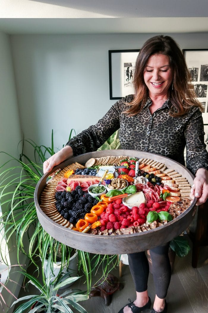 woman holding a big board of charcuterie with colorful foods