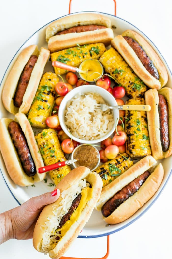 holding a Summer Bratwurst with Sauerkraut in front of a Summer Brats and Sauerkraut Tray