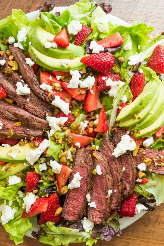 beautiful salad with marinated flank steak, strawberries, and goat cheese