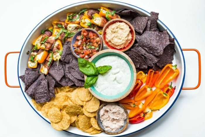 oval platter of chips with hummus, ranch dressing, salsa, and peppers