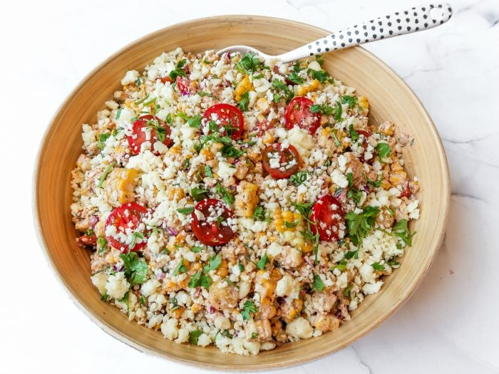 a serving bowl of summer corn tomatoe salad garnished with cilantro and cheese