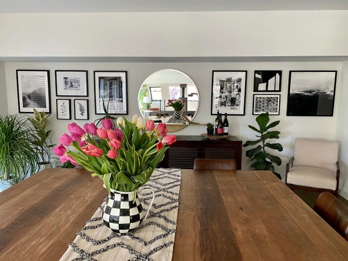 tulips on a table with black and white photos on the wall
