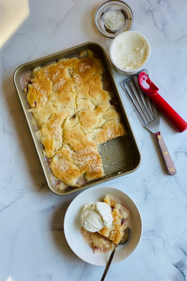 9x13 pan of peach cobbler with a serving, and vanilla ice cream