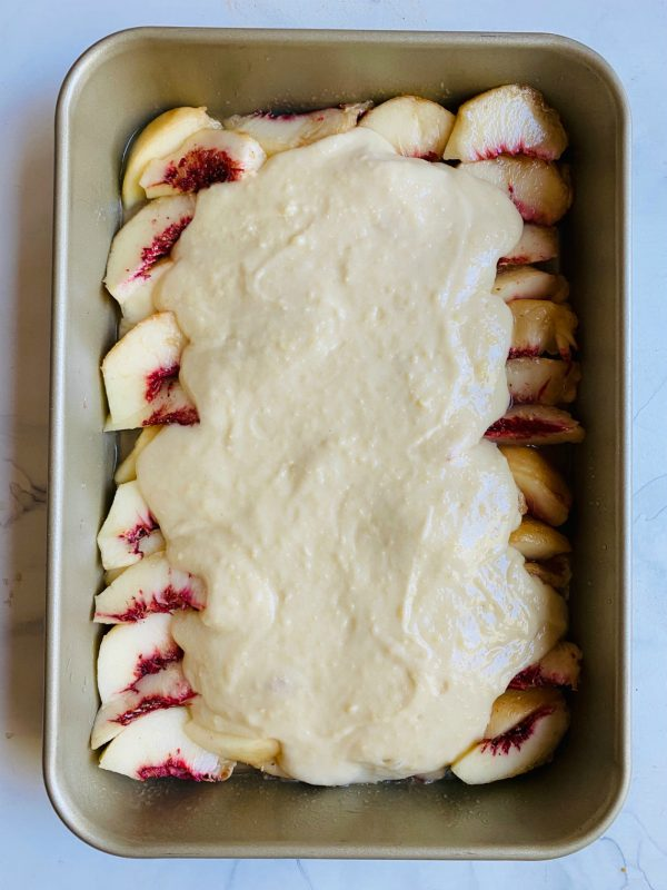 fresh white peaches with cobbler topping, before baking