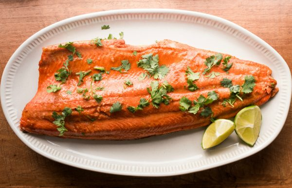 one wild alaskan salmon filet on a plate, garnished with lime