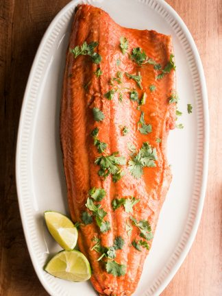 one large salmon filet on a white plate, cooked with lime and garlic, garnished with lime and cilantro