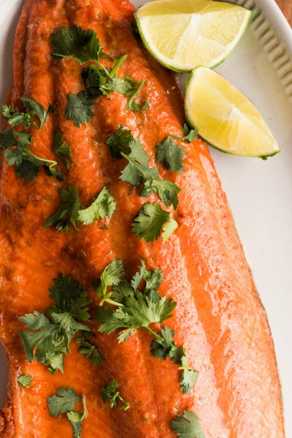 close up wild alaskan salmon filet, garnished with lime and cilantro
