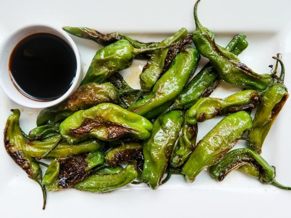 a dozen grilled Shishito Peppers