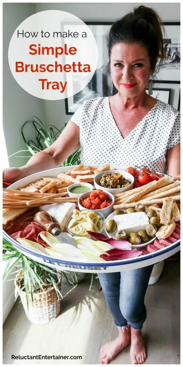 woman holding a tray with bruschetta, cheese, and crackers